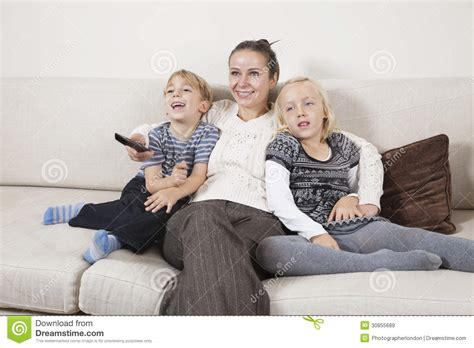 sofa for watching tv happy young woman with children on sofa watching tv stock