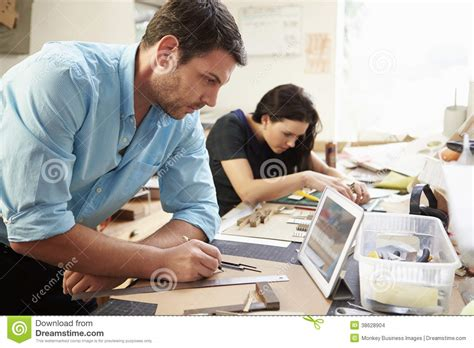 male architect with digital tablet studying plans in two architects making models in office using digital