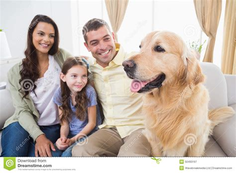 golden retriever family family sitting with golden retriever on sofa stock photo image 50493197