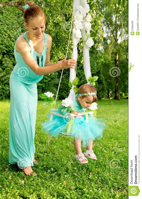 baby on a swing mother and baby on a swing on nature stock photo image