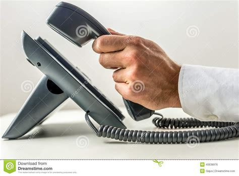 male hand picking up the receiver of a telephone stock