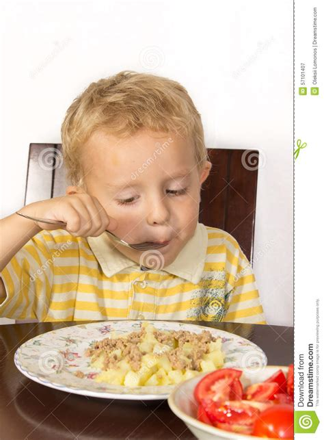 only eats from blond boy trying to eat with a fork potatoes with and tomatoes stock photo image