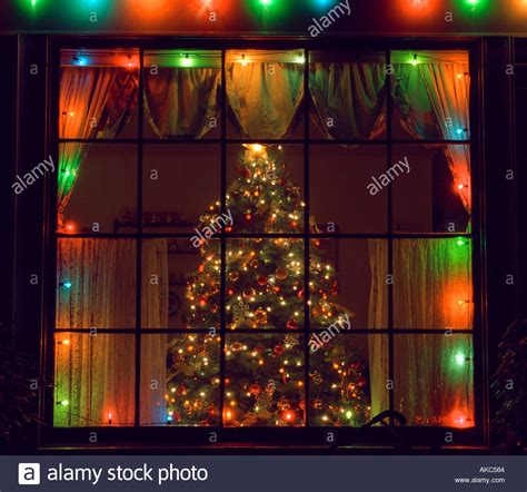christmas tree through home window stock photo royalty