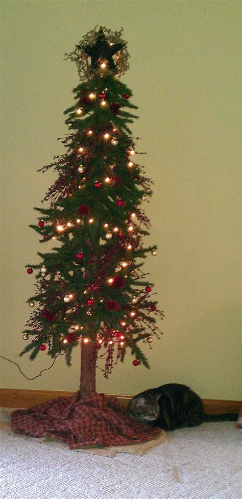 primitive christmas tree decorated with red pip berry