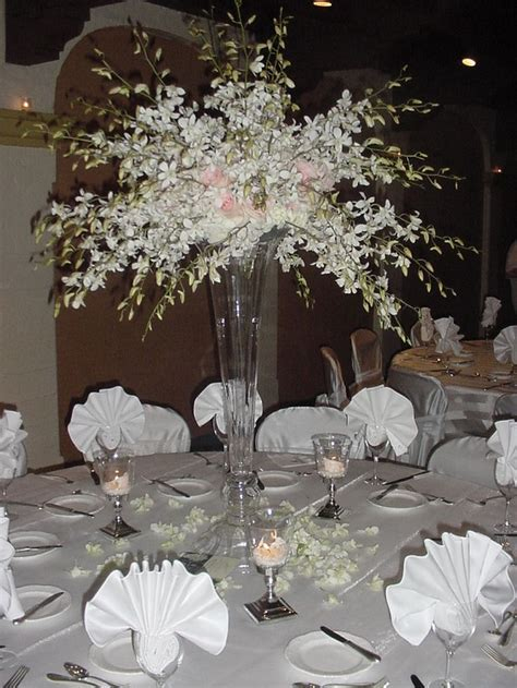 White dendrobium orchid sprays in a tall vase. Check on