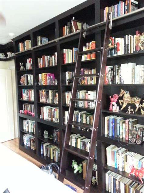 built in bookcases with rolling ladder and vault