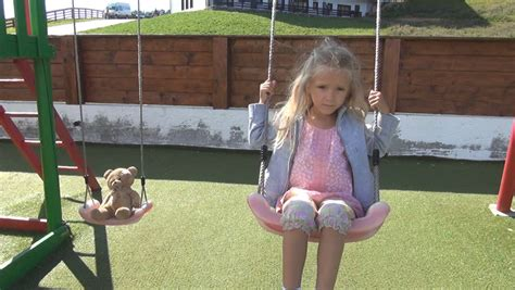 Child Swinging A Teddy Bear Girl Playing With Her Toy On