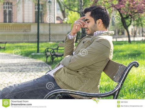 man on the bench headache tiered man sitting in a park on bench stock