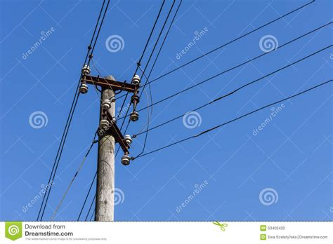 blue wires in electricity wooden electric pole with wires in the blue sky in the