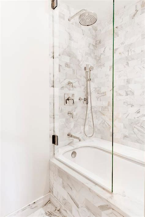 bathtub with glass marble subway tiled tub with glass shower partition transitional bathroom
