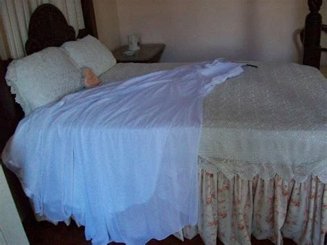 My wedding dress laying on the bed in the Great House
