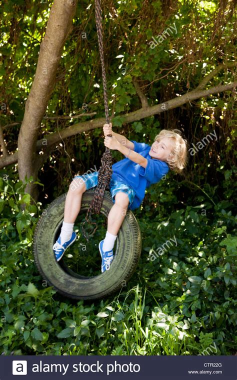 swinging images boy swinging on a tire swing stock photo royalty free