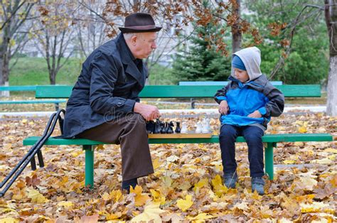 back bench boys grandfather playing chess with his little boy royalty free