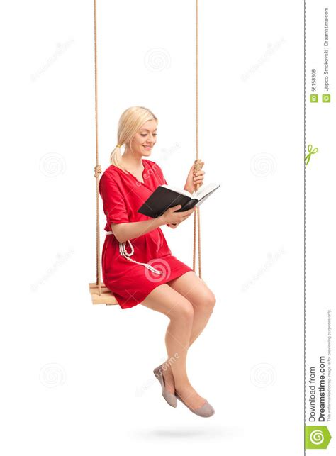 women and swinging young woman sitting on a swing and reading a book stock