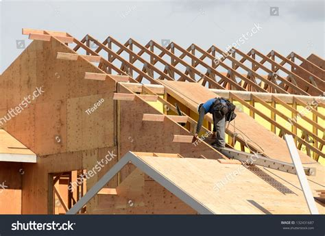 timber outrigger roof construction crew working on roof sheeting stock photo