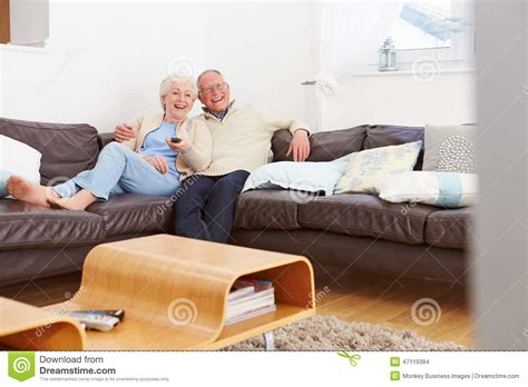 sofa for watching tv senior couple sitting on sofa watching tv stock photo