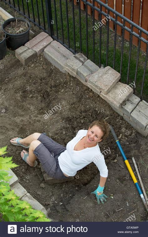 backyard cleaning happy smiling woman doing yard maintenance cleaning up the