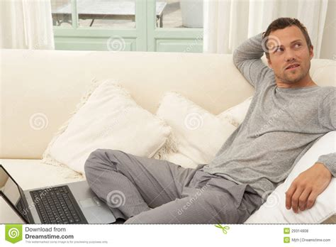 man on the couch young attractive man on couch with laptop at home royalty