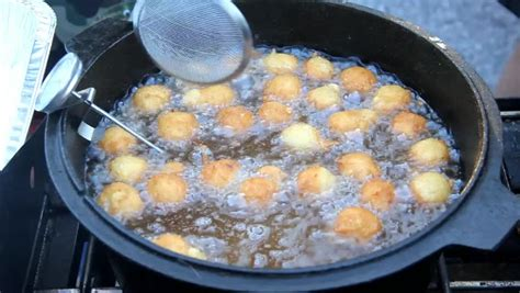 cookout hush puppies fish in boiling cooking being stirred at evening cookout stock footage