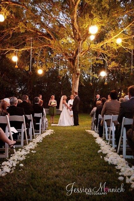 getting married under a willow tree at dusk all lit up