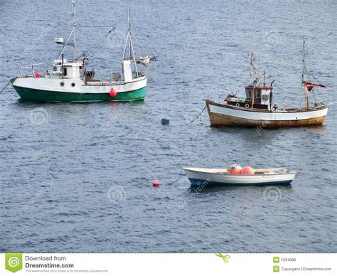 een boot twee visserijschepen en een boot op anker stock foto