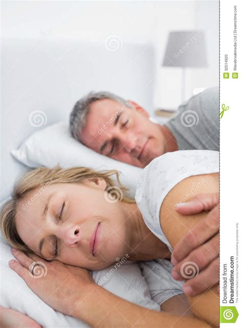 spooning in bed peaceful couple sleeping and spooning in bed stock photo