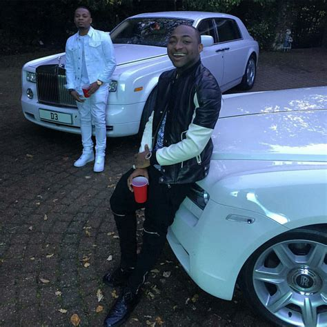 roll royce nigeria photo olamide and davido poses in front of white