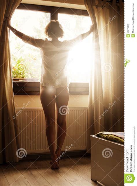 her bedroom window her bedroom window woman looking at sunrise through window