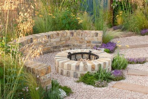 garden firepit fireplace of brick with pebble patio in circular with pathway wall ornamental