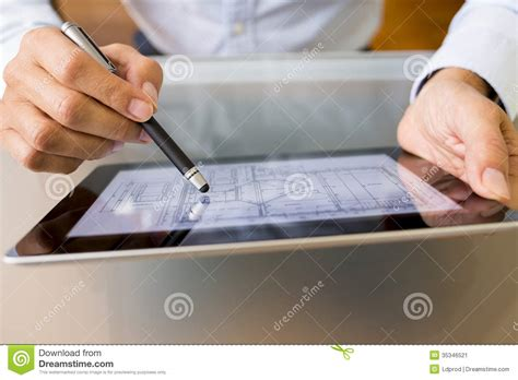 male architect with digital tablet studying plans in architect working with stylus and digital tablet pc stock