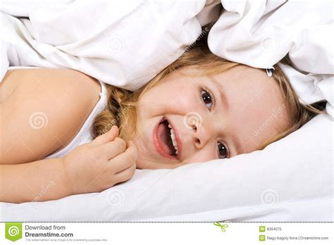 lay on the bed little girl laying in bed under the quilt royalty free