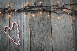 christmas lights and heart shaped candy canes on rustic