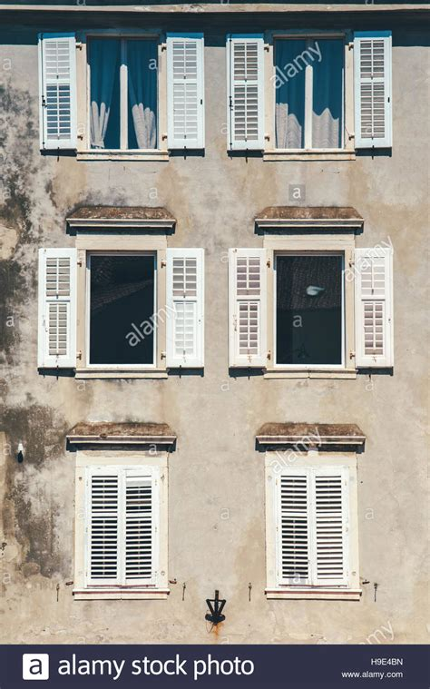 classic venetian window shapes create architecturally weathered building facade and old windows with classic