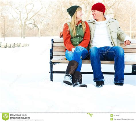 couple sitting on bench young couple sitting on a bench during winter stock image