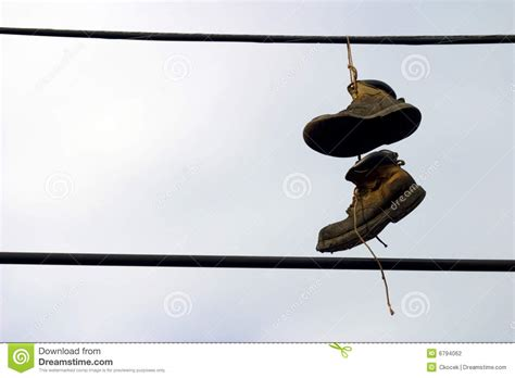 hanging photos on wire shoes hanging from a telephone wire stock photography