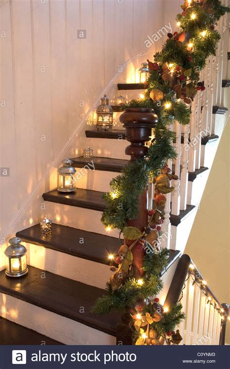 garland for stair banister lanterns and christmas garlands adorn a wooden staircase and banister stock photo