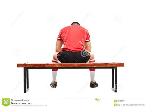 sad bench sad football player sitting on a wooden bench stock photo