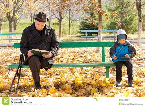 sitting on a park bench elderly man and small boy sitting on a park bench royalty