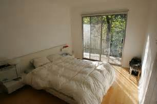minimlaist small bedroom with white bed cover wooden floor