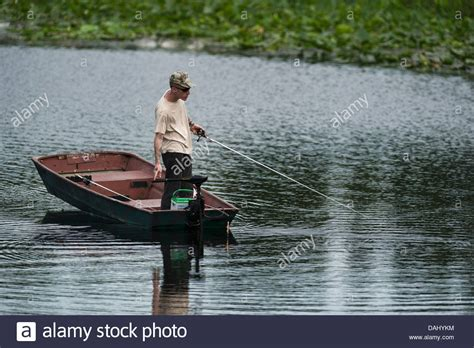 man fishing in boat a thin man standing and fishing from a small row boat on