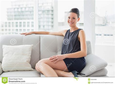 sitting on sofa smiling well dressed woman sitting on sofa at home stock