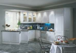 white cabinets with glass doors on white