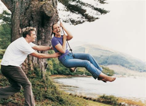 2 couples swinging couple playing on a rope swing man pulling woman stock