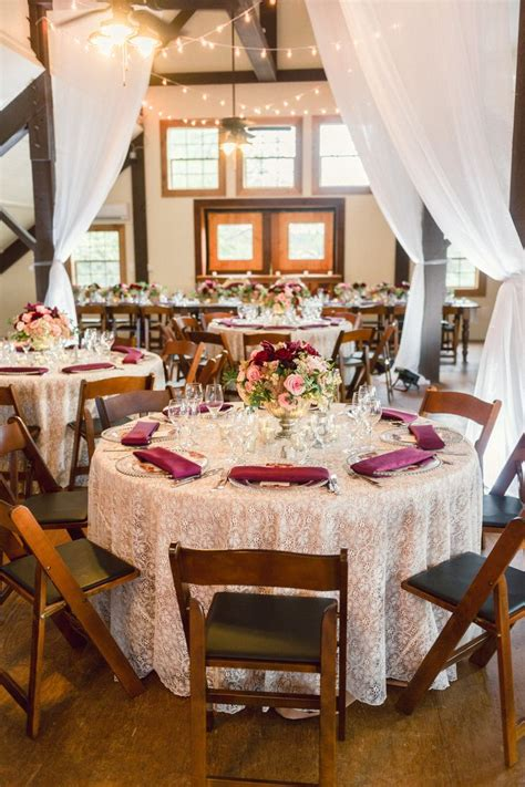 the barn reception at tower winery was draped with white linens and illuminated with