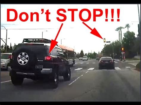 yellow light on car car begins stopping at intersection before yellow light