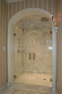 Large glass wall and door placed on the cream tile wall plus shower