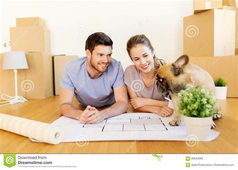 moving to a new house with a dog couple with boxes blueprint and dog at new home stock photo image 99530366