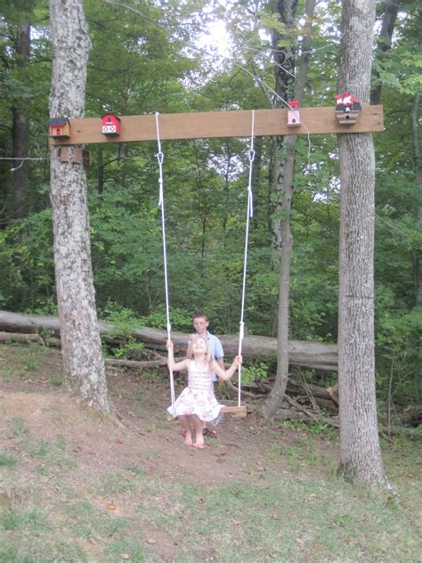 a tire swing hanging from a branch designed to dwell our take on a nature playscape