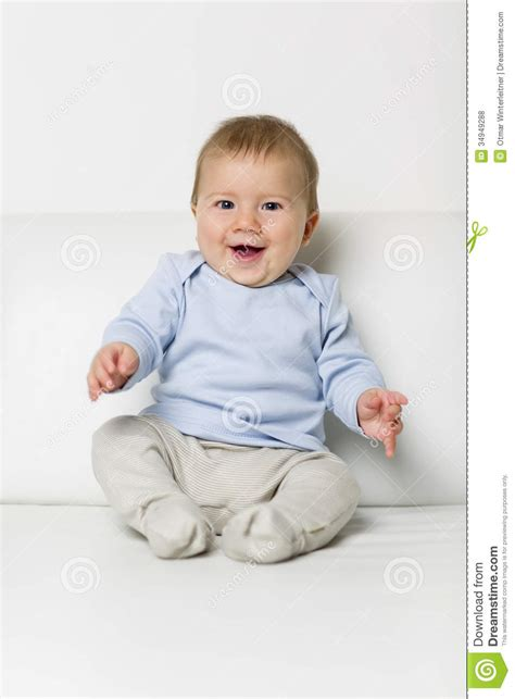 couch baby portrait of sweet overjoyed baby boy sitting on sofa