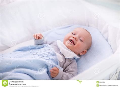 baby boy in a crib knitted blanket stock photo